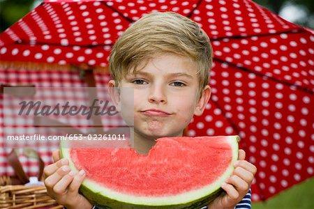 Un jeune garçon tenant une tranche de melon d'eau avec un morceau manquant