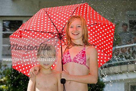 Deux enfants debout sous un parapluie dans leurs maillots de bain