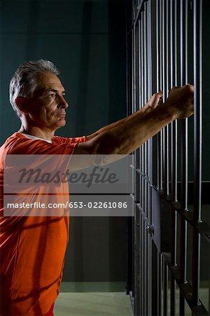 Un prisonnier debout dans sa cellule de prison