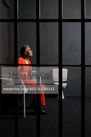 Un prisonnier assis dans sa cellule de prison