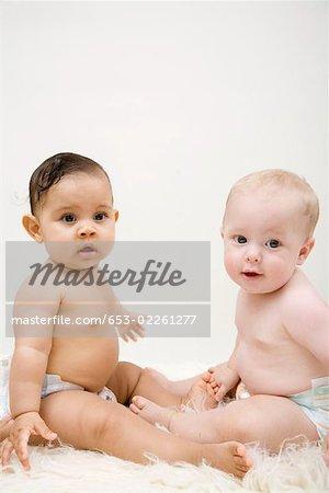 Zwei Babys sitzen von Angesicht zu Angesicht, Blick in die Kamera