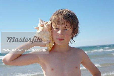 Boy Holding Seashell to His Ear, Elmvale, Ontario, Canada