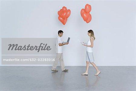 Jeune homme et une femme marchant vers l'autre, les ordinateurs portables transport et ballons coeur