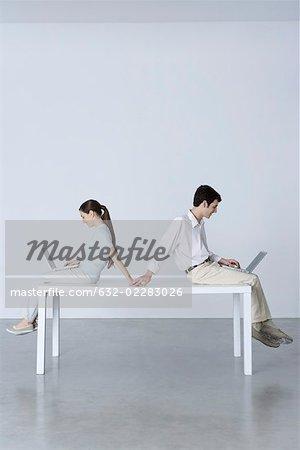 Séance de couple dos à dos, à l'aide d'ordinateurs portables, main dans la main