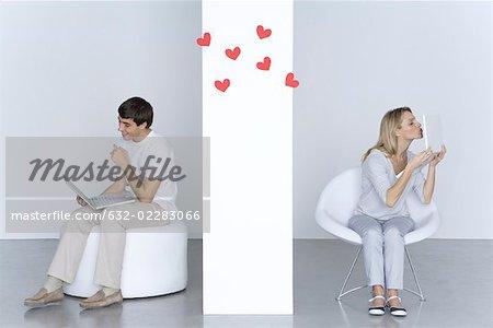 Femme embrasse l'ordinateur portable, l'homme regardant son propre ordinateur portable et souriant, coeurs en l'air entre eux