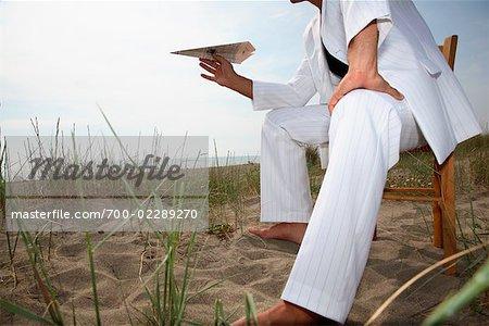 Mann, hält Papierflieger am Strand