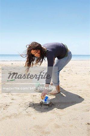 Jeune fille, collecte des ordures sur la plage