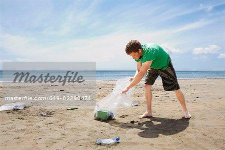 Jeune homme, collecte des ordures sur la plage