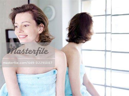 Woman sitting next to mirror smiling