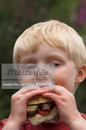 Kind eine Wurst in ein Brötchen auf einem Grill Essen