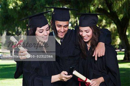 College Graduates Looking at Cellular Phone