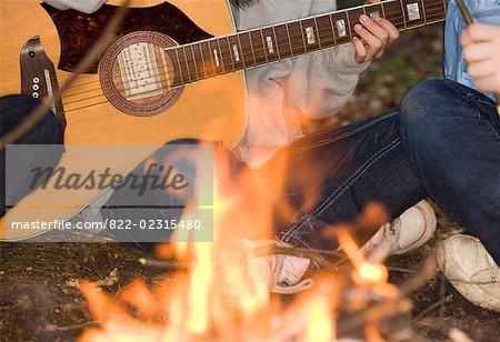 Gros plan du feu de camp avec des gens assis croisés à pattes jouer de la guitare - headless
