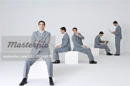 Geschäftsmann Lächeln in die Kamera mit Armen gefaltet, während seine Klone Laptops im Hintergrund verwenden