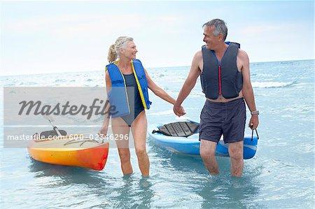 Homme et femme apportant Kayakas hors de l'eau