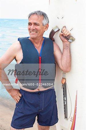 Portrait of Man Holding Windsurfer Board