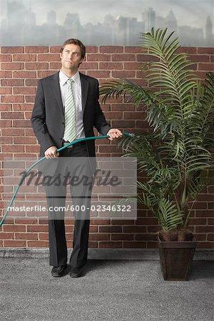 Homme d'affaires d'arrosage des plantes