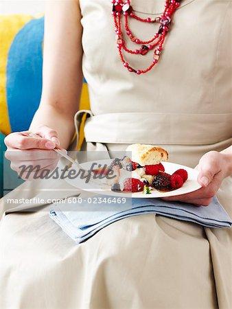 Femme avec un gâteau, des baies et crème glacée