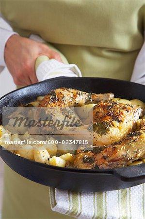 Gros plan des cuisses de poulet grillées, oignons grillés et pommes de terre dans la poêle en fonte