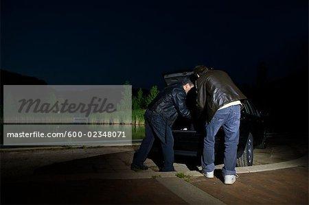 Hommes sans quelque chose de coffre de voiture pendant la nuit