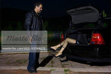 Homme regardant le cadavre dans le coffre de la voiture