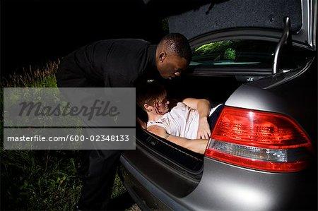 Placer le corps dans le coffre de la voiture de l'homme