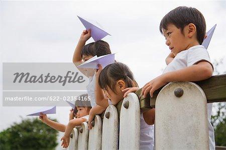 Kinder werfen Papier Flugzeuge