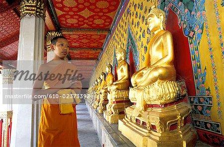 Thaïlande, Bangkok, Wat Arun temple, jeune moine stagiaire en prière par une rangée de statues de Bouddhas