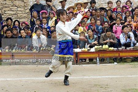 China, Sichuan, near Danba, Tibetan village festival, dancer in traditional costume