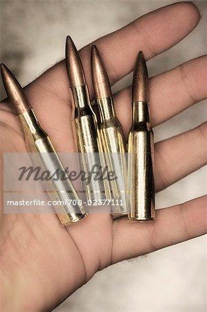 Homme tenant des balles de 12,7 mm