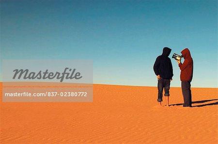 Vue arrière de deux personnes debout dans un désert et à l'aide d'une caméra vidéo, Lake Mead, Utah, USA
