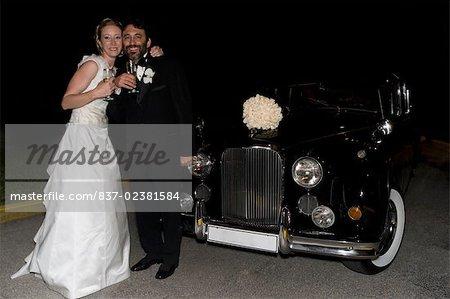 Portrait d'un couple de jeunes mariés permanent et buvant champagne
