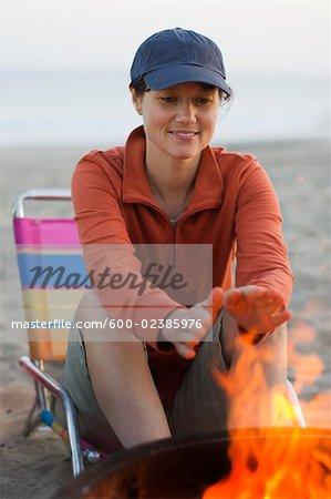 Femme assise par un feu de camp, Santa Cruz, Californie, USA
