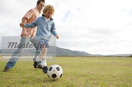 Père et fils (6-7 ans), jouer avec le ballon de soccer sur champ faible angle vue