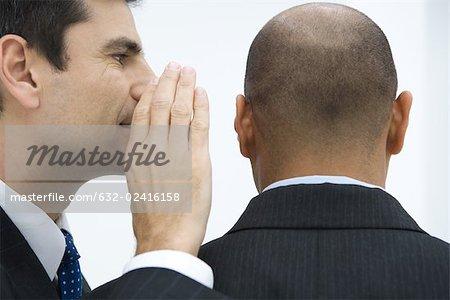 Homme d'affaires chuchotant à l'oreille de collègue, gros plan