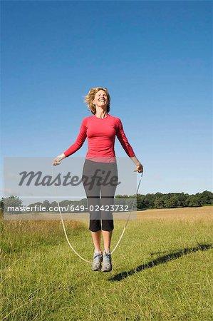Femme sautant dans le champ