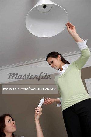 2 women changing lightbulb