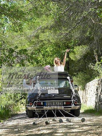 Mariée et le marié en agitant de voiture de mariage
