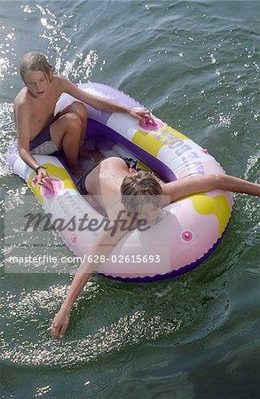 Deux garçons dans un caoutchouc bateau - amitié - jeunesse - temps libre - lac