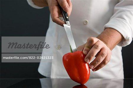 Nahaufnahme einer Chef Hand hält ein roter Pfeffer und den Kern entfernen, mit einem Messer