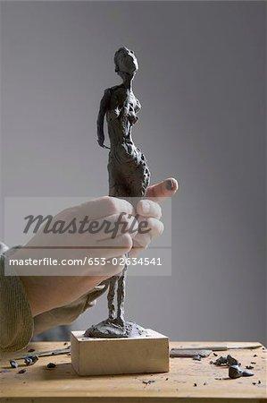 Main de l'homme travaillant sur une sculpture