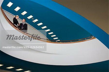 Zwei Geschäftsleute stehen auf dem Balkon und Händeschütteln