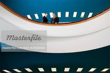 Zwei Geschäftsleute, die auf einem Balkon stehend
