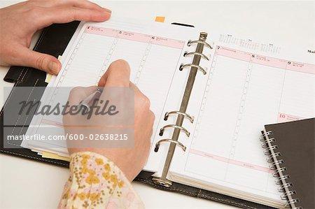 Mains écrivant dans Agenda