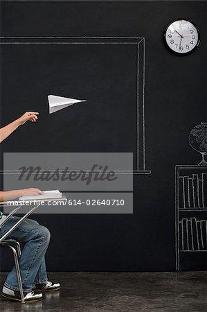 Ein Junge wirft eine Papierflieger