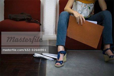 Femme tenant fichier, assis avec les jambes dehors, recadrées
