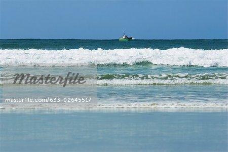 Sea shore, fishing boat on horizon