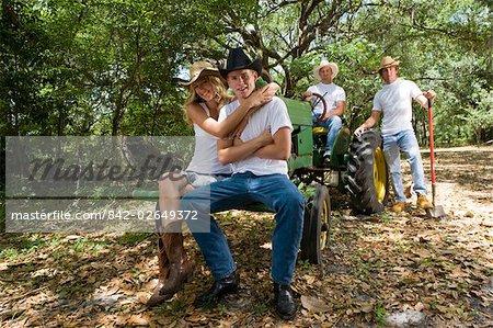 Portrait de jeunes cow-boys et cow-girl relaxant près de plein air tracteur