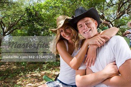 Portrait de jeune couple adultes portant des chapeaux de cow-boy en plein air