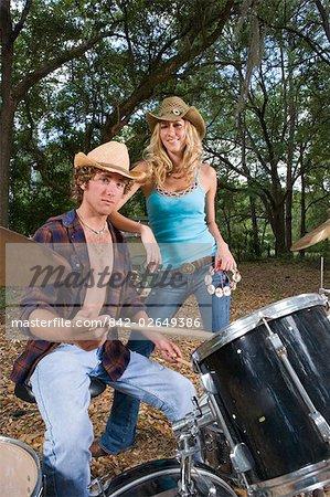 Jeune cow-boy jouant de la batterie et cowgirl tenant un tambourin à l'extérieur