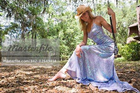 Portrait de jeune femme blonde en robe du soir et chapeau de cowboy, assis sur une balançoire en plein air